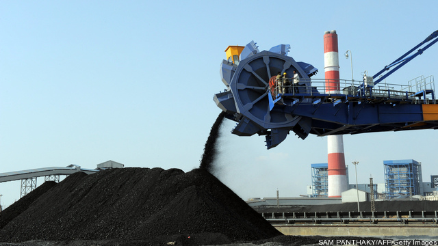 Workers use heavy machinery to sift through coal at the Adani Power company thermal power plant, India's first supercritical 660 MW unit.  (Photo by SAM PANTHAKY/AFP/Getty Images)