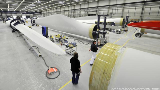 Workers walk past giant wind turbine bla