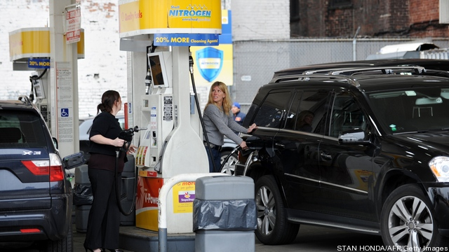 People pump gasoline at a Shell station