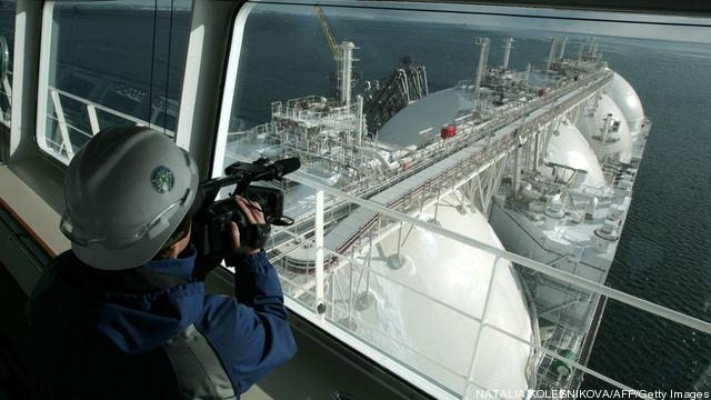 A cameraman films an LNG tanker docked a