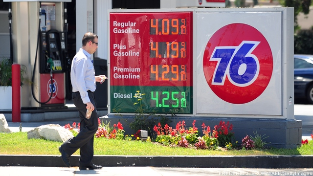 A man walks past gas prices posted on a