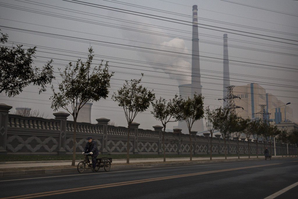A man rides a bicycle as a coal-fired power plant in Beijing is seen in the background in a November 2014 photo..  Photo by Kevin Frayer/Getty Images.