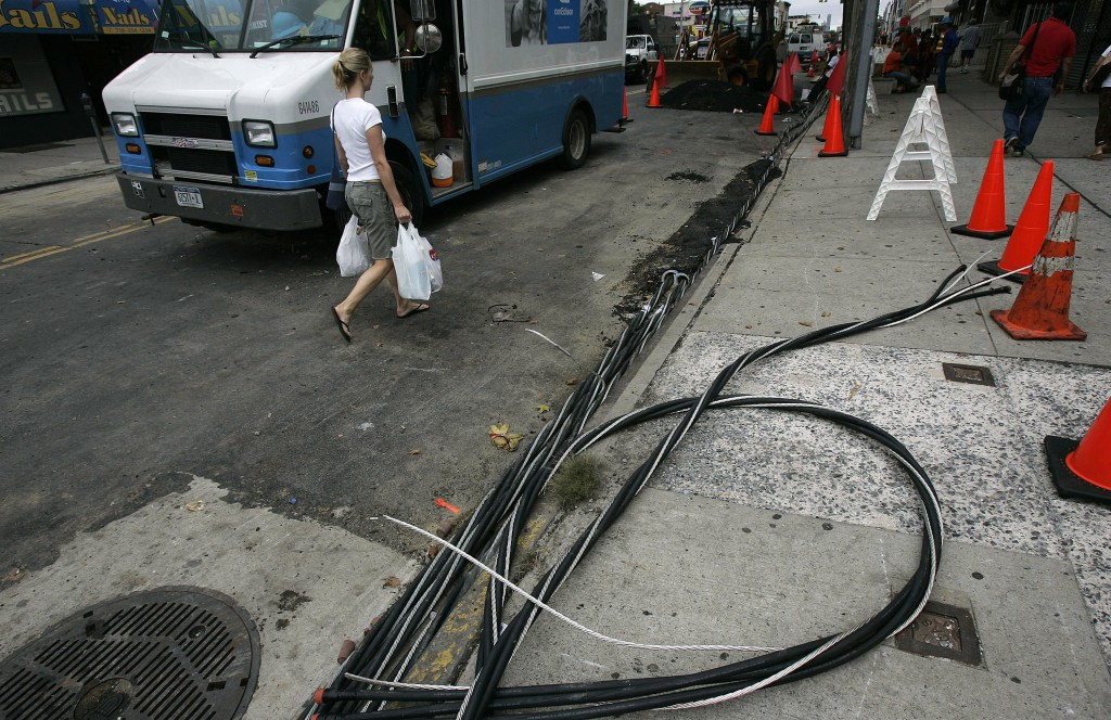 NEW YORK - JULY 23:  A woman walks past power lines on the sidewalk as workers try to restore electrical service July 23, 2006 in the Queens borough of New York City. Many Con Edison and other electrical workers have been working long hours attempting to restore power to thousands of people that were left without electricity after a blackout a week ago.  (Photo by Chris Hondros/Getty Images)